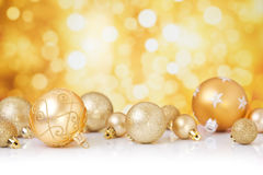 Christmas scene with gold baubles, gold background. Golden Christmas baubles in front of defocused golden lights Stock Photography