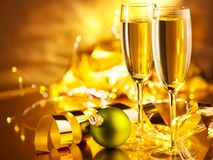 Christmas scene. Holiday champagne over golden glow background. Christmas and New Year celebration. Two flutes with sparkling wine royalty free stock photo