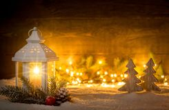 Christmas scene with a lantern, trees, fir branch and blurred lights in front of an illuminated dark wooden board as copy space Stock Photography
