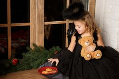 Christmas scene. portrait of a little blond girl, in a black angel costume stealing Santa`s cookies near the window. Royalty Free Stock Image