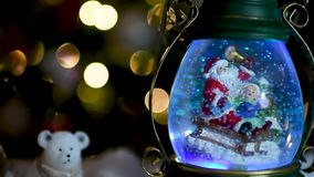 Christmas scene, Santa with child on a sleigh in snow dome. With reindeer, polar bears and snowmen domes and candles, illuminated christmas tree in background stock video footage