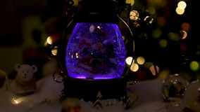 Christmas scene, Santa with child on a sleigh in snow dome. With reindeer, polar bears and snowmen domes and candles, illuminated christmas tree in background stock video