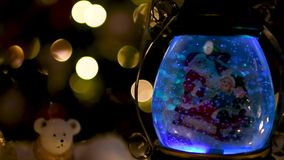 Christmas scene, Santa with child on a sleigh in snow dome. With reindeer, polar bears and snowmen domes and candles, illuminated christmas tree in background stock footage