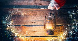 Christmas scene. Santa Claus hand holding vintage oil lamp royalty free stock photos