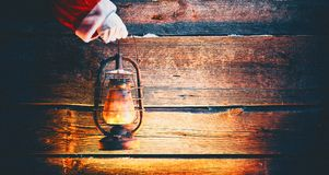 Christmas scene. Santa Claus hand holding vintage oil lamp stock photography