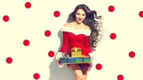 Christmas scene. Sexy Santa. Beauty model girl holding gifts. Christmas scene. Sexy Santa. Beauty model girl wearing red party costume holding gifts Stock Photos