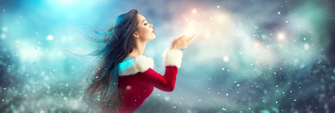 Christmas scene. Beauty brunette young woman in santa party costume blowing snow. Christmas scene. Santa. Brunette young woman in party costume blowing snow over royalty free stock photos