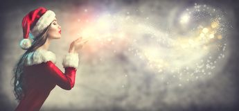 Christmas scene. Santa. Brunette young woman in party costume blowing snow. Over holiday blurred background stock photos