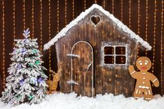 A Christmas scene with a snow-covered hut, a gingerbread man and a Christmas tree. Fairytale forest decoration. A New year scene with a snow-covered wooden hut Royalty Free Stock Photo