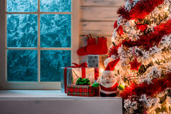 Christmas scene with tree gifts and frozen window Stock Photo