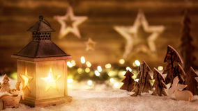 Christmas scene in warm lantern light. Cozy Christmas arrangement with beautiful wooden ornaments on snow in the warm candlelight of a nice lantern, low-key Royalty Free Stock Photo