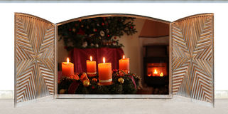 Christmas scenery - view through wooden open doors. Romantic christmas scenery, view through wooden doors. chimney fire and advent wreath stock photos