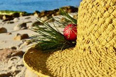 Christmas by the sea, red gold glitter Christmas decoration on a straw hat, Christmas in July royalty free stock photography