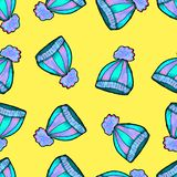 Christmas seamless pattern drawn by hand. Blue knitted hat on a yellow background. Happy new year stock illustration