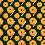 Christmas seamless pattern with oranges and candy canes on dark green background. watercolor holiday illustration. Stock Photo