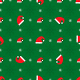 Christmas seamless pattern. With red hats on green background Stock Image