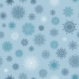 Christmas seamless pattern from red andblue snowflakes on a blue background. Royalty Free Stock Image