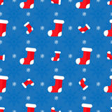 Christmas seamless pattern. Red socks on blue background Stock Image