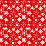 Christmas seamless pattern with white snowflakes on a red background. Royalty Free Stock Images