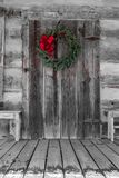 Christmas Wreath Hung on the Log Cabin Door. Christmas season photo of a wreath with big red ribbon hung on the log cabin door royalty free stock image