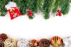 Christmas seasonal border of holly, ivy, mistletoe, cedar leaf sprigs with pine cones and gold baubles Stock Photo