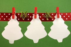 Christmas and seasonal holidays bunting with white Christmas treas hanging from pegs on a line with copy space Royalty Free Stock Photos