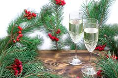 Christmas seasonal still-life of champaign, pine branches, red b. Christmas and New Year seasonal composition with pine tree branches, two glasses of champaign royalty free stock photography