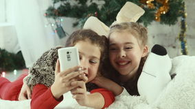 Christmas selfie of two girls. Two girls make selfie on the background of Christmas tree stock video