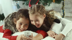 Christmas selfie of two girls. Two girls make selfie on the background of Christmas tree stock video footage