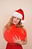 Christmas sensual girl with a big heart present, in Santa costume Stock Photo