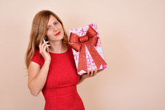Christmas sensual girl with a present, calling on the phone Stock Images