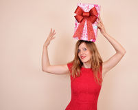 Christmas sensual girl with a present on the head, in red costume Royalty Free Stock Photography