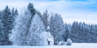 Christmas serene panoramic landscape tiny chapel in snowy frozen forest Stock Image