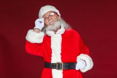 Christmas. Serious Santa Claus in white gloves adjusts her glasses and stares into the camera. Isolated on red. Background royalty free stock photos