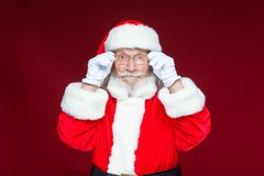 Christmas. Serious Santa Claus in white gloves adjusts her glasses and stares into the camera. Isolated on red. Background royalty free stock images