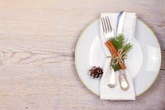 Christmas set with plate, cutlery, pine branches, cinnamon and red berries on wooden place. Winter holidays and festive background stock photo