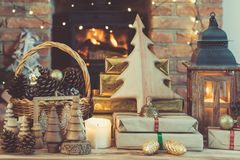 Christmas setting, lantern, decorated fireplace, fur tree. Christmas composition, lantern, presents and handmade wooden decorations on the table in front of Stock Photos