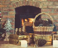 Christmas setting, lantern, decorated fireplace, fur tree. Christmas composition, pine cones in wicker basket, wooden ornaments, presents on the table in front Stock Image