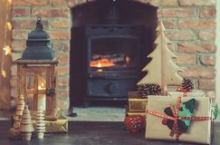 Christmas setting, lantern, decorated fireplace, fur tree. Presents, Christmas lantern and handmade wooden decorations on the table in front of fireplace with Royalty Free Stock Photos