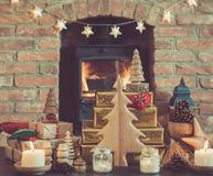 Christmas setting, lantern, decorated fireplace, fur tree. Christmas settinig, lantern, presents and handmade wooden ornaments on the table in front of fireplace Stock Images