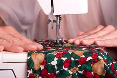 Christmas Sewing. Close up capture of Seamstress sewing a holiday theme piece of material Stock Image