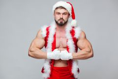 Christmas. Santa Claus . Young muscular man wearing Santa Claus hat demonstrate his muscles. Muscular Fighter Stock Photo