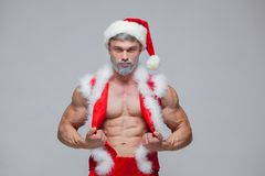Christmas. Sexy Santa Claus . Young muscular man wearing Santa Claus hat demonstrate his muscles. Stock Photo