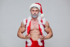 Christmas. Sexy Santa Claus . Young muscular man wearing Santa Claus hat demonstrate his muscles. Royalty Free Stock Photo