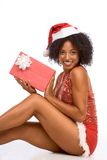 Christmas sexy Santa present. New year celebration. Sexy ethnic woman in Christmas Mrs. Santa Claus outfit holding wrapped gift box and sitting on floor Stock Image