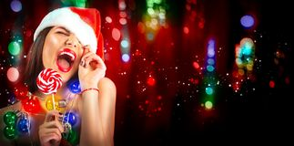 Christmas woman. Beauty model girl in Santa`s hat with with lollipop candy in her hand over holiday background. Christmas woman. Beauty model girl in Santa`s hat royalty free stock photo