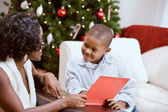 Christmas: Sharing A Christmas Story Book. African American mother and child celebrate Christmas with a Christmas tree, gingerbread house and presents Royalty Free Stock Image