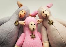 Christmas sheep. Three christmas toy sheep on grey background Stock Photography