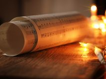 Christmas sheet music. On an old wooden table with Christmas lights, romantic scene with selective focus stock images