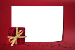 Christmas sheet of paper. With small gift on red  background Royalty Free Stock Photos